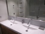 Une double vasque, un radiateur sèche-serviette, un miroir, une baignoire