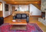 Une table basse, un canapé, une table, des chaises, une cuisine équipée
