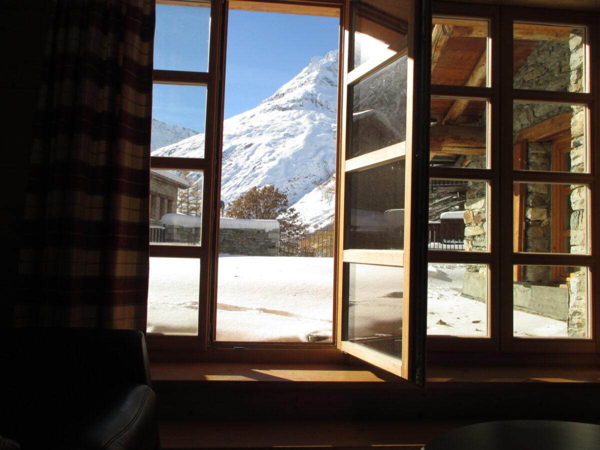 Une fenêtre ouvrant sur une terrasse enneigée et des montagnes