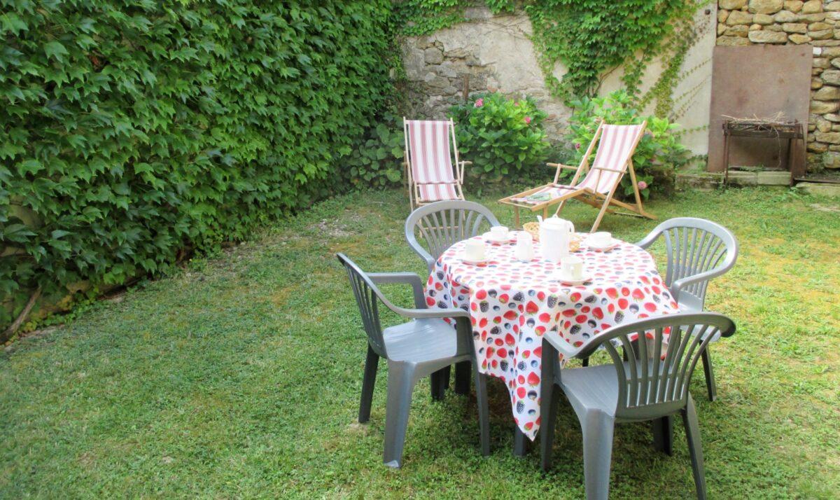 Un jardin, une table, des chaises, des chaises longues, un barbecue
