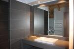 Une vasque, un miroir, un radiateur sèche-serviettes