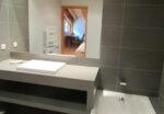 A sink, a mirror, a bathtub, a heated towel rail