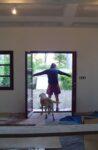 Un homme ouvrant une porte-fenêtre et un chien