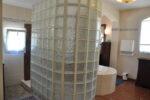 Une douche entourée d'un mur de verre, une baignoire