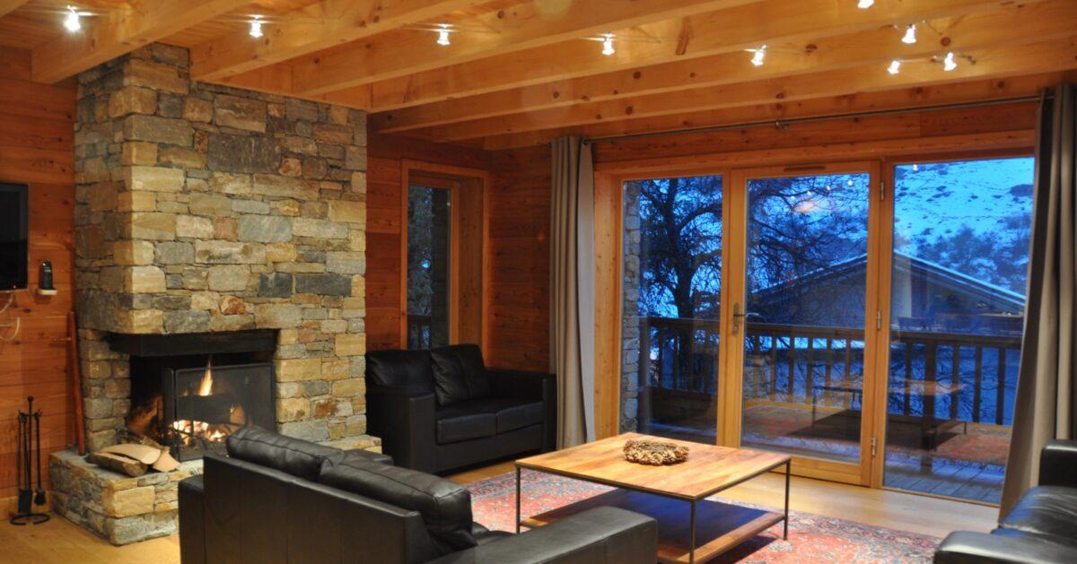 Une cheminée, des canapés, une table basse, une baie vitrée