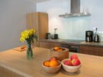An equipped kitchen, a table, fruits, flowers