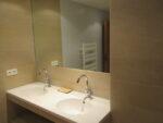 Une vasque double, un miroir, un radiateur sèche-serviettes