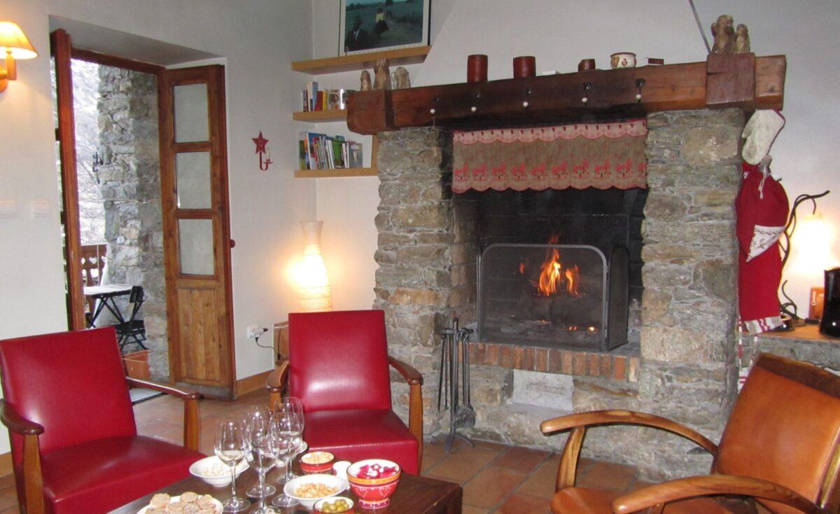 Une table basse, des fauteuils, une cheminée, une porte-fenêtre