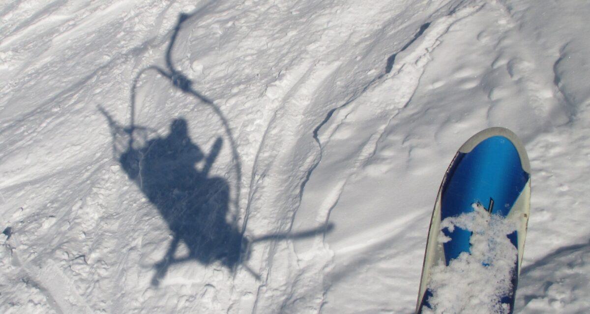 L'ombre sur de la neige poudreuse d'un skieur sur un télésiège