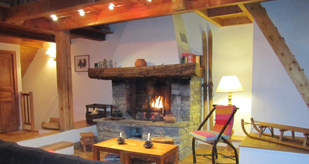 Une cheminée, un canapé, un fauteuil, une table basse