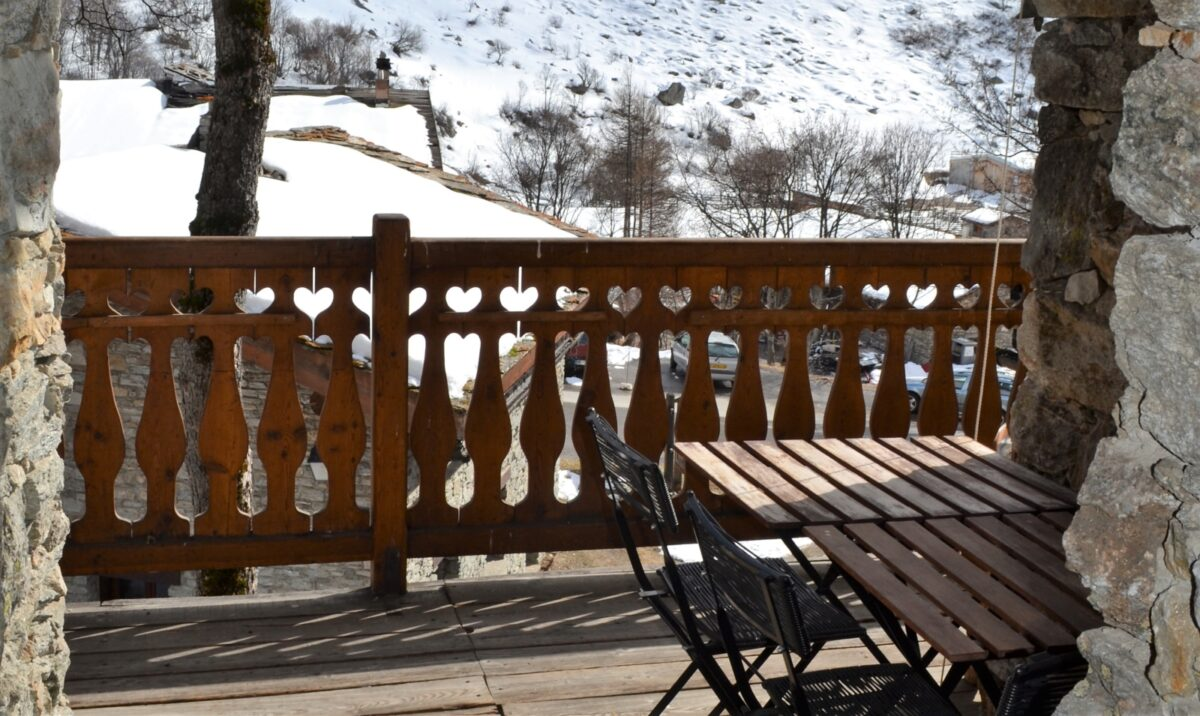 Un balcon, une table, des chaises, une montagne enneigée