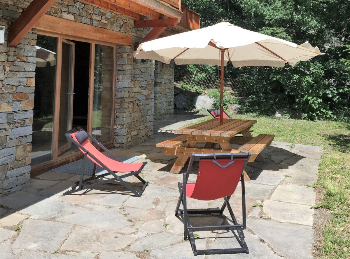 Une terrasse, une table, des bancs, des relax, un parasol, un jardin