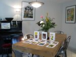 Des tableaux, des cartes postales, un piano, une table, des chaises