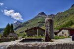 Une fontaine, une maison, des montagnes