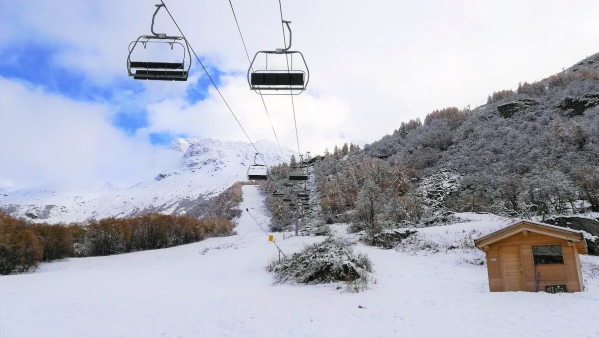 A ski slope, a stoped chairlift, snow
