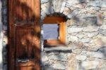 Un volet en bois, des pierres, une petite fenêtre