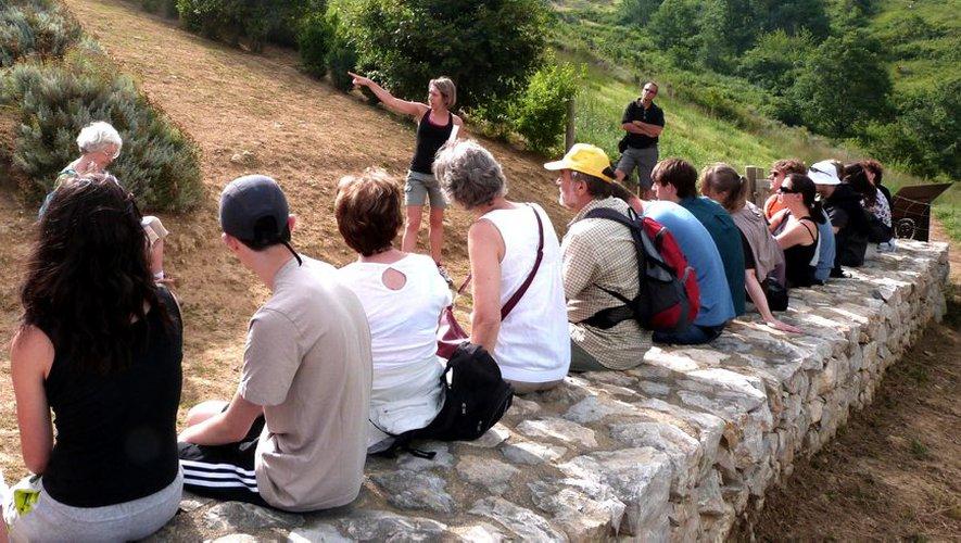 Touristes assis sur un mur écoutant une conférencière
