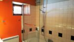 Une baignoire, une colonne de douche, un pare-douche, une fenêtre