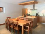 Une cuisine équipée, une table, des chaises