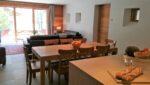 Une table, des chaises, des canapés, une baie vitrée