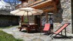 Une terrasse, des relax, une table de jardin, un parasol, un tas de bois