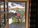 Une porte-fenêtre, une terrasse, une table ronde, un parasol, des chaises, des relax