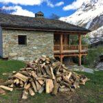 Un tas de bois, un chalet de pierre avec un toit en lauzes