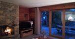 Un feu de cheminée, un téléviseur, la vue sur une terrasse à la nuit tombante