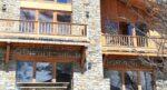 Un chalet de pierre et de bois, des baies vitrées reflétant la montagne enneigée