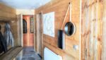 Une porte avec vitrail, une porte en bois, un porte-manteau, un banc, un miroir, une carte en relief
