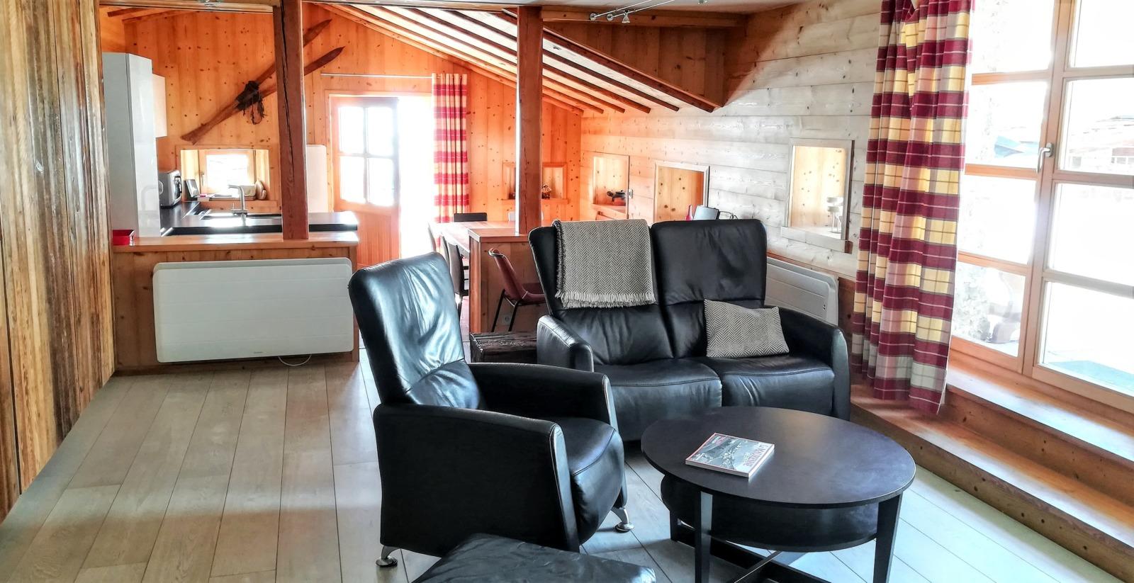 Un canapé, un fauteuil, un pouf, une table basse, deux porte-fenêtres