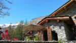 Un chalet de pierre et de bois, une terrasse clôturée, des montagnes, des arbres