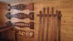 """Des panneaux de bois indiquant """"Restaurant"""", """"Salon de thé"""", """"Artisanat"""", """"Glaces"""", une luge ancienne"""
