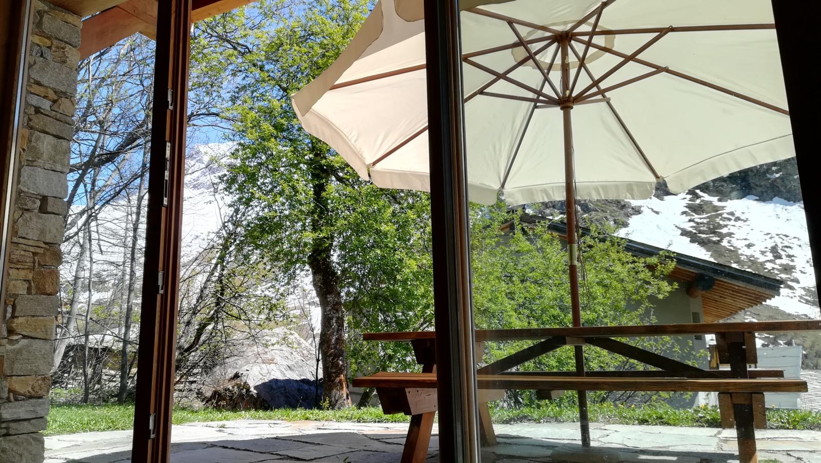 Un parasol, un arbre, des montagnes et une table vus à travers une baie vitrée