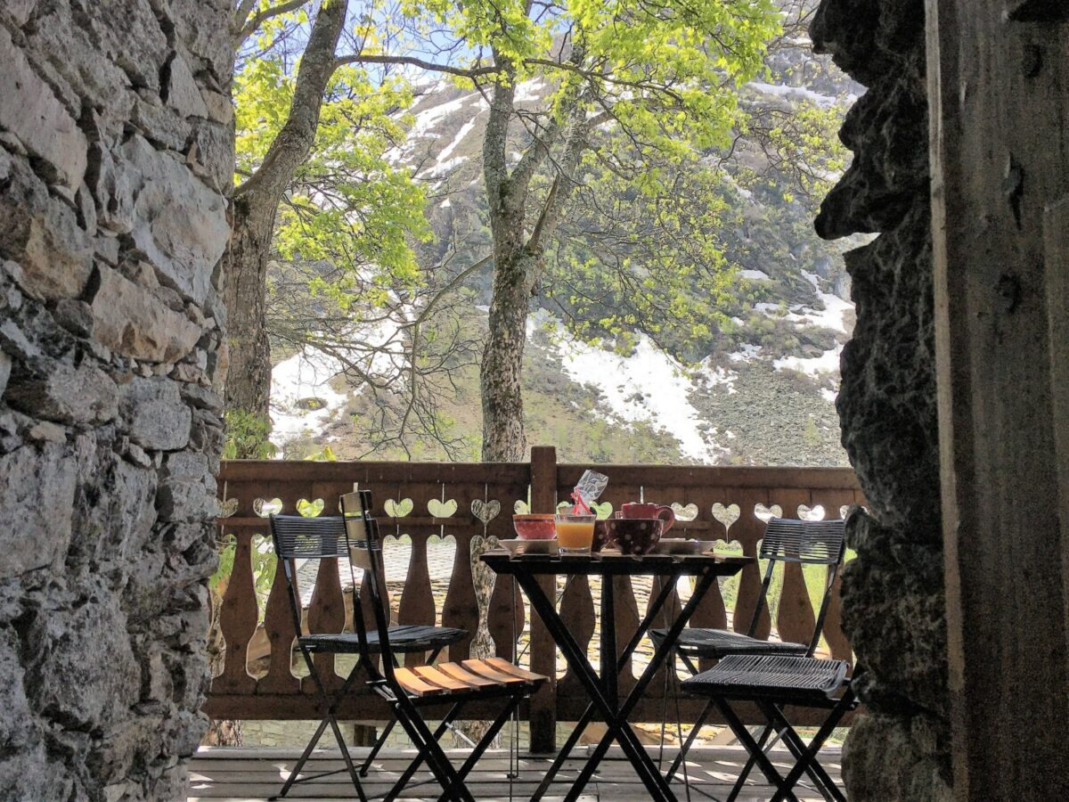 Une table sur une terrasse, un arbre, des montagnes