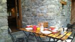 A table set for breakfast, a stone wall, a French window