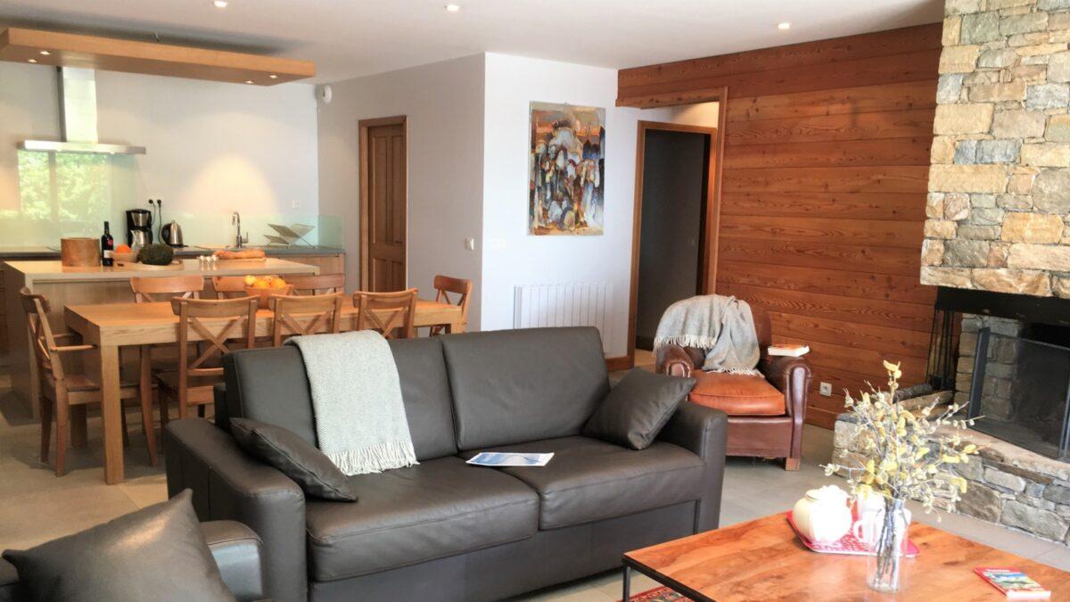 Une cuisine équipée, une table, des chaises, des canapés, une table basse, une cheminée