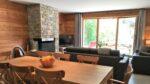 Une table, des chaises, des canapés, une cheminée, un téléviseur, une baie vitrée