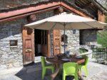 Un chalet de pierre et de bois, une table ronde, des chaises, un parasol