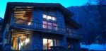 A chalet lit up at nightfall