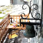 A balcony, a table set for breakfast, a copper bell
