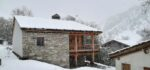 Un chalet, de la neige, des montagnes, un téléski, des pistes de ski