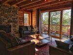 Une table basse, trois canapés, une baie vitrée, un balcon, des relax
