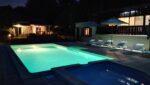 An illuminated swimming pool, deckchairs, parasols