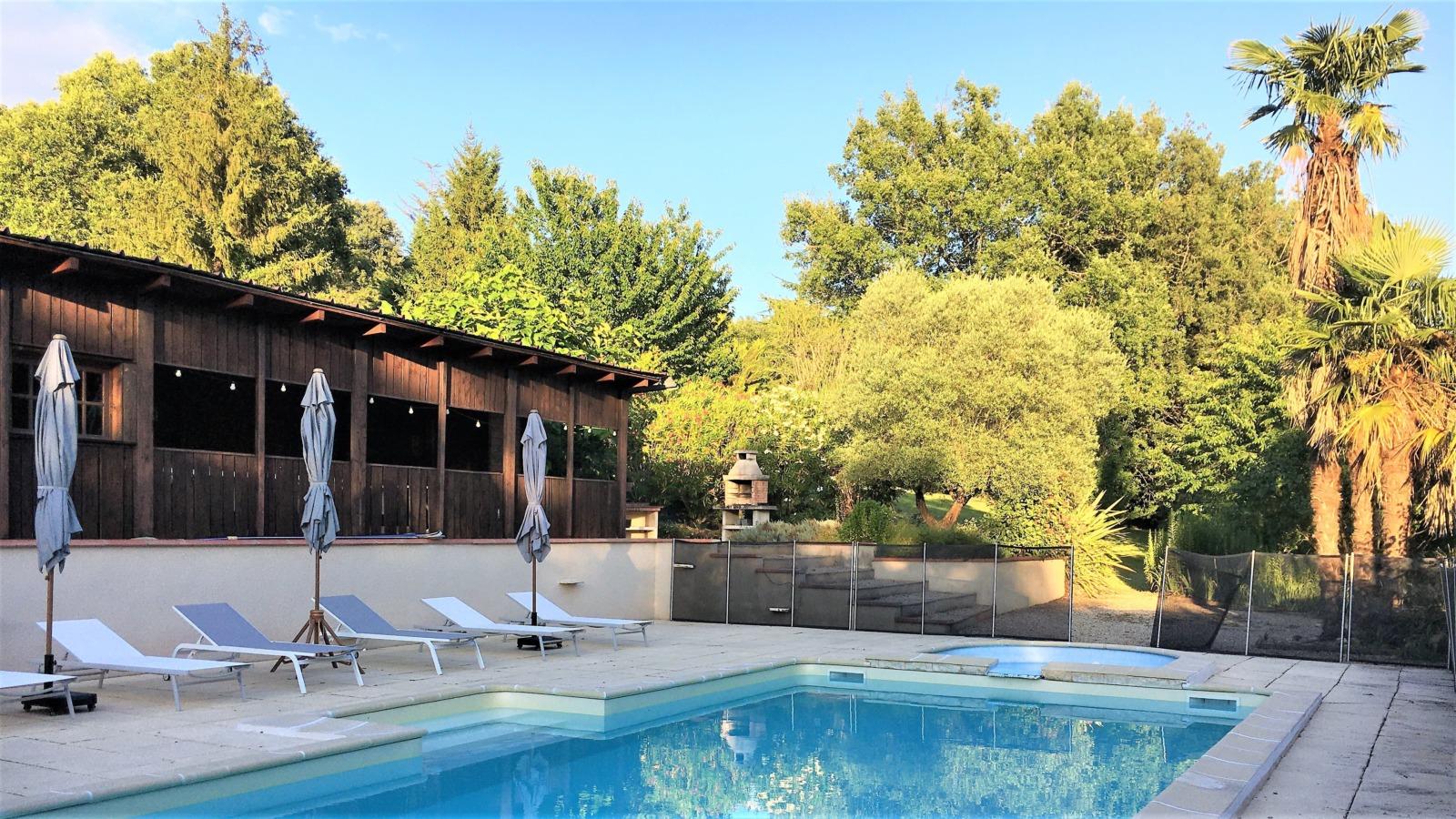 Une piscine, des transats, des parasols, un barbecue, des arbres, du beau temps